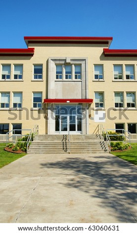 Brick building entrance with cement walkway and sky. Can be school, small hospital, retirement home.