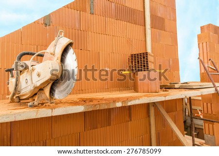 Brick by Brick,  build a house on your own. Building a home. Power tools on the dusty construction site. House under construction. - stock photo