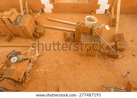 Brick by Brick,  build a house on your own. Building a home. Power tools on the dusty construction site. House under construction - stock photo