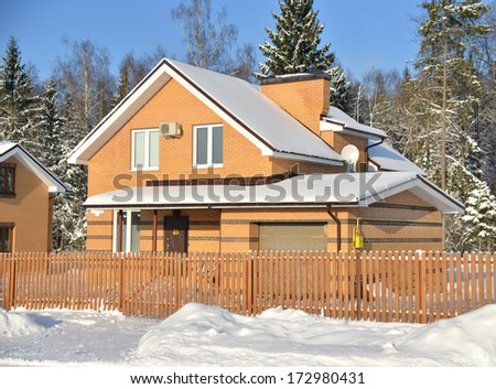Brick cottage house in winter time close to forest - stock photo
