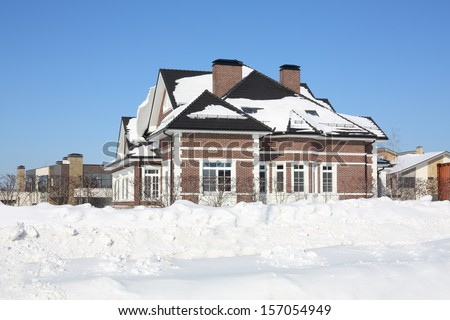 Brick cottage with big window at frosty and sunny winter day. - stock photo