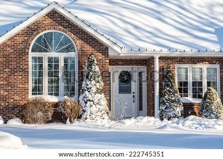 Brick detached home buried in snow and decorated for Christmas. - stock photo