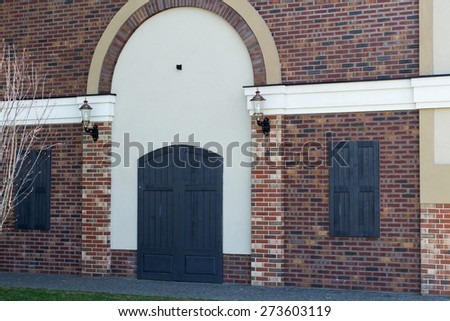 brick facade with wooden door and windows shuttered, street lights on the wall on either side of the door - stock photo