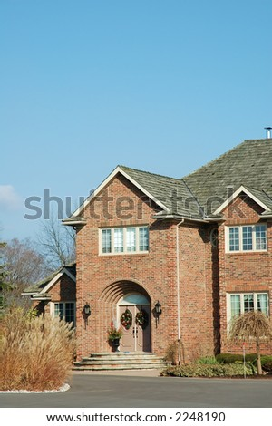 Brick home entrance with Christmas wreaths on front door. - stock photo