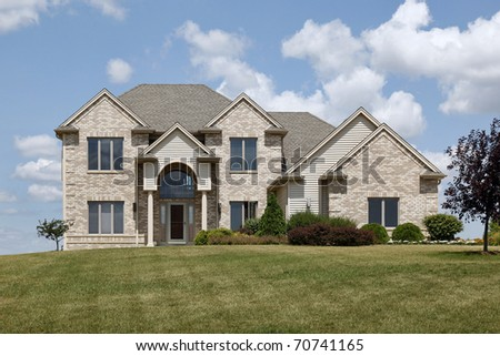 Brick home in rural neighborhood with arched entry - stock photo