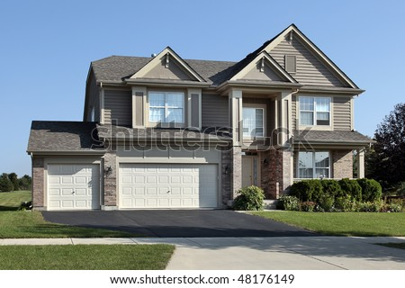 Suburban Home Beige Siding Double Garage Stock Photo
