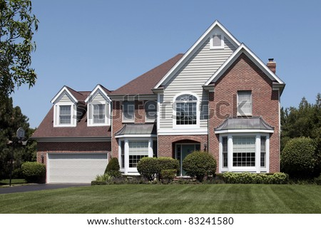 Brick home in suburbs with arched entry - stock photo