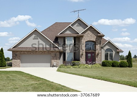 Brick home in suburbs with arched entryway - stock photo