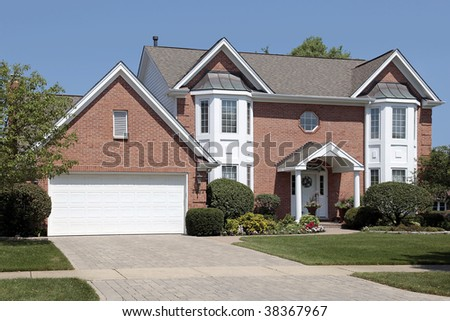 Brick home in suburbs with columns in entryway