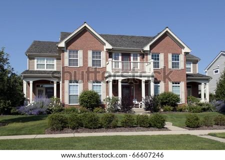 Brick home in suburbs with front balcony - stock photo
