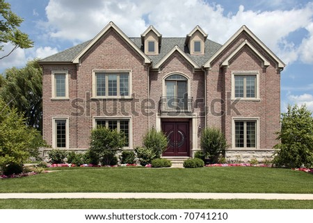 Brick home in suburbs with front balcony