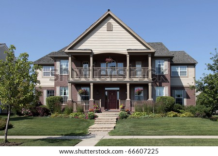 Brick home in suburbs with large front balcony - stock photo