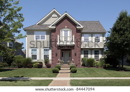 Brick home with beige siding and front balcony - stock photo