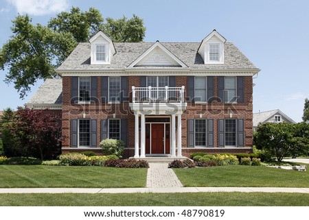 Brick home with columned entry and front balcony - stock photo