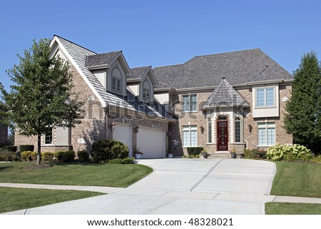 Brick home with red wood door and three car garage - stock photo