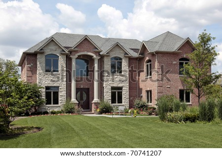 Brick home with stone front and white columns - stock photo
