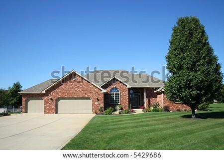 brick home with three car garage - stock photo