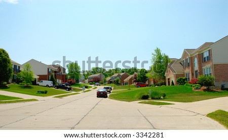 Brick homes line the street in a suburban upscale neighborhood in summer time. - stock photo
