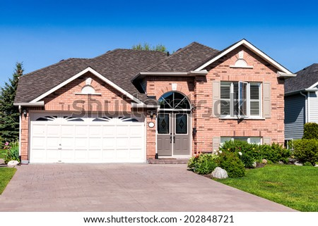Brick house with a lawn and driveway - stock photo
