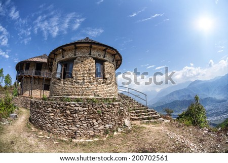 Brick house with stairs at mountains background on Sarangkot hill, Pokhara, Nepal - stock photo
