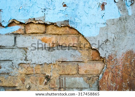 Brick old weathered wall with cracked painted plaster as a background - stock photo