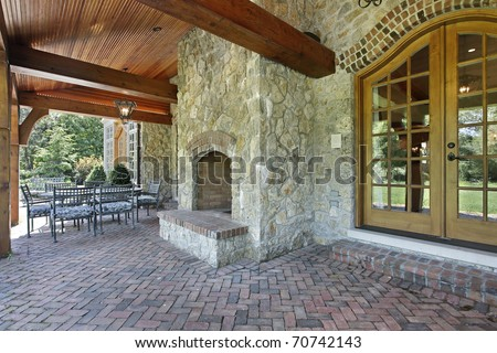 Brick patio outside luxury home with stone fireplace - stock photo