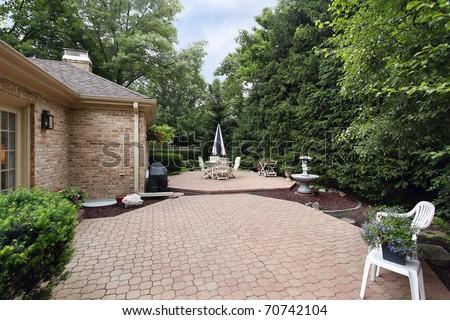 Brick patio with rock garden and fountain - stock photo