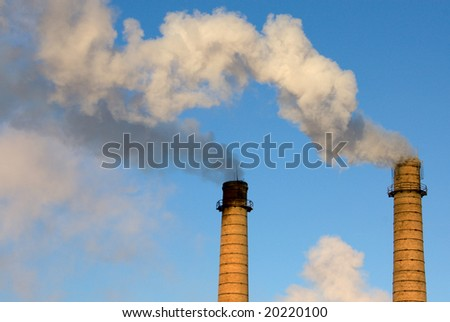 Brick pipes with a smoke on a background of the clear blue sky