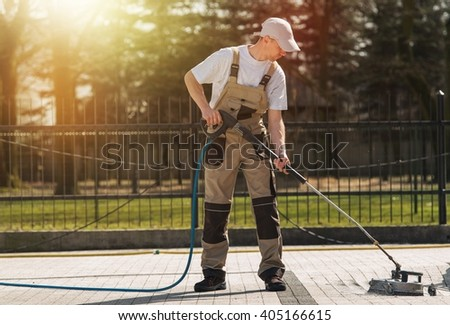Brick Residential Roadway Cleaning by Professional Cleaning Worker. High Pressure Water Mechanical Brick and Pavements Cleaning Service Theme. - stock photo