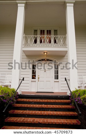 Brick steps leading up to the front door of a white columned wood siding house
