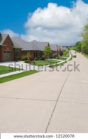 Brick Suburban Home in Summer along a long winding street. - stock photo