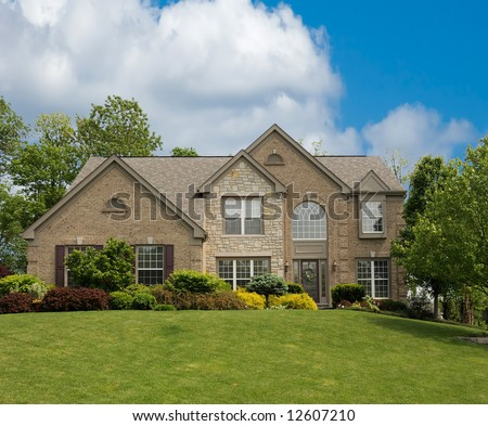 Brick Suburban Home with beautiful landscaping, on a sunny summer day. - stock photo
