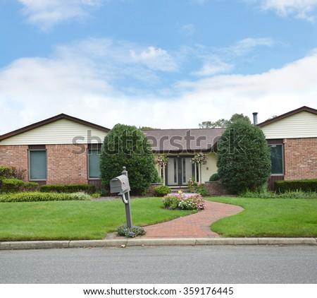 Brick Walkway Mailbox to Suburban Brownstone brick Ranch Style Home Residential neighborhood Blue Sky clouds USA - stock photo