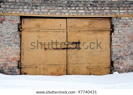 Brick wall and gates in winter - stock photo