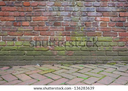 Brick wall and tiled pavement - stock photo