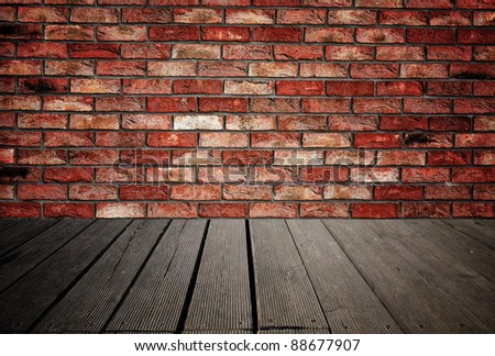 Brick wall and wood planks in old interior useful as background - stock photo
