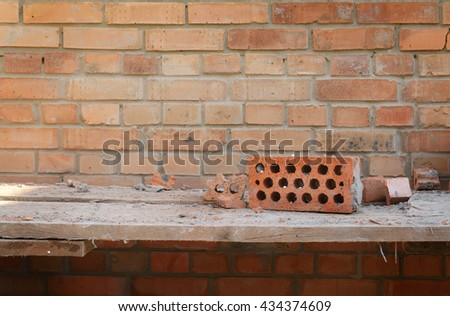 Brick wall and wooden shelf on the construction territory