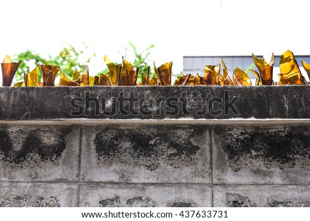 Brick Wall covered with broken glass pieces - stock photo