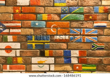 brick wall covered with number of flags - stock photo