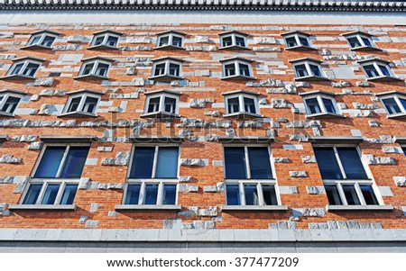 Brick wall facade of building with rock details - stock photo