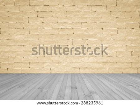 Brick wall in light yellow cream beige color tone with wooden floor textured background in dark grey color tone