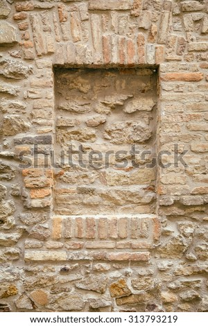 Brick Wall of an Old House with Brick-encased Window - stock photo