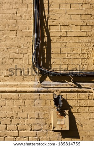 brick wall with a bundle of electrical wiring - stock photo