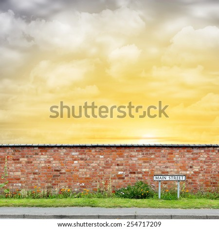 Brick Wall with a Main Street Sign and Sunset, Sunrise. - A manipulated photograph with some illustration elements. - stock photo