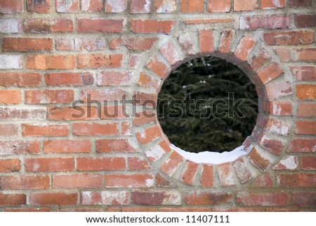 Brick wall  with a round window - stock photo