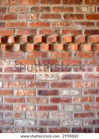 brick wall with an accent pattern in the top - stock photo