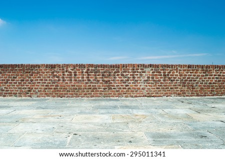 brick wall with blue sky background - stock photo