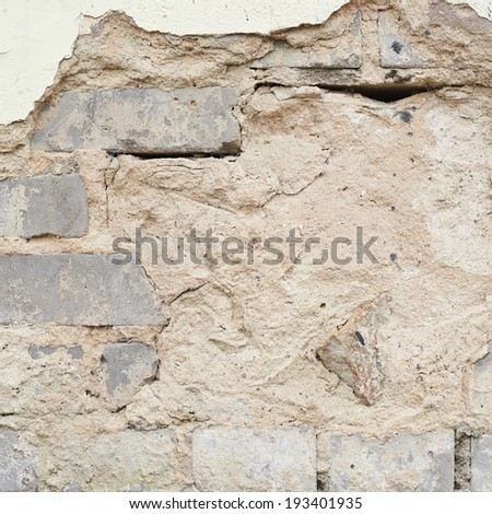 Brick wall with the whitewash falling off fragment as a background texture - stock photo