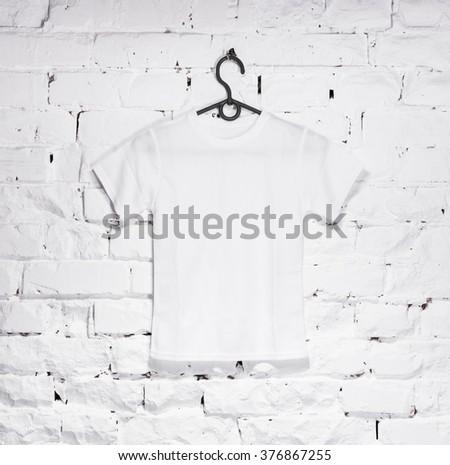 brick whitewashed wall with white t-shirt on hanger - stock photo