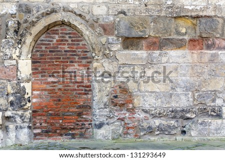 Bricked up doorway in a stone wall, York, England. - stock photo